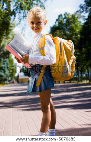 First-former girl is going to school carrying backpack and holding a book - stock photo