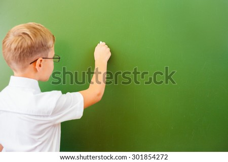 First grade schoolboy wrote on blackboard with chalk at classroom. Little boy dressed in a white shirt and wearing glasses. Concept of knowledge day and first of september.
