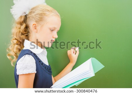 First grade schoolgirl holding a notebook and wrote on blackboard with chalk at classroom. Little girl dressed in a school uniform. Concept of knowledge day and first of september