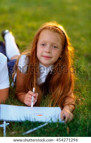 first grader writes at the blackboard - stock photo