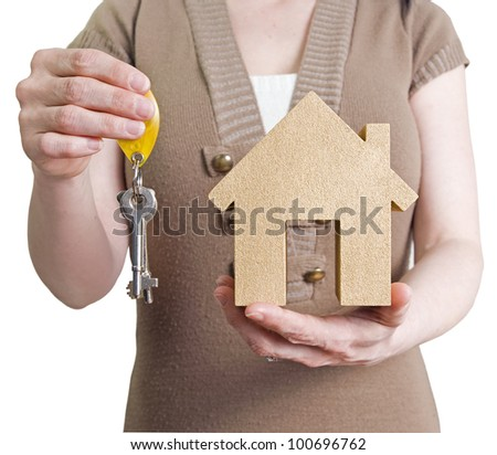 first house, woman holding golden house and door keys to show property purchase - stock photo