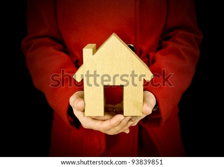 first house, woman holding golden house to show property purchase - stock photo