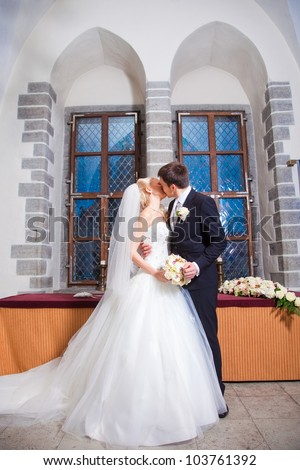 first kiss of beautiful groom and bride during wedding ceremony in old town hall interior - stock photo