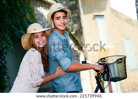 first love happy young couple teenager sightseeing together in summer with a bicycle - stock photo
