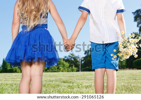 First love. Nice little boy keeping the bunch of flowers  and holding the hands with girl.   - stock photo