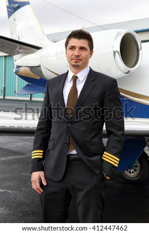 First officer of the small jet plane with one hand in the pocket