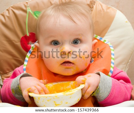 First one-year infant's meal by himself - stock photo