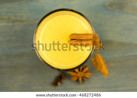 First person perspective top down view on turmeric latte with cinnamon sticks and anise herb on wooden table