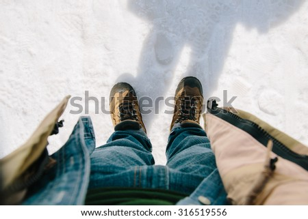 First-person view. Man bend down the head looking for his boots standing on snow - stock photo