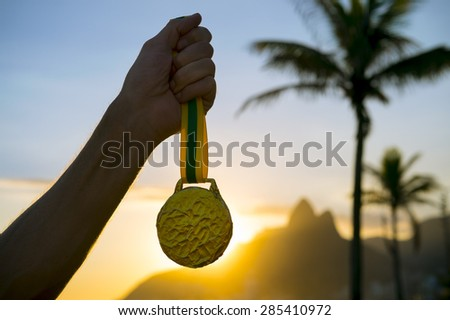 First place athlete holding gold medal in front of the sunset on Ipanema Beach Rio de Janeiro Brazil  - stock photo