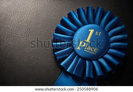 First place award rosette over dark background with copy space - stock photo