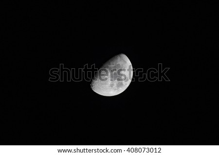 First Quarter Moon Phase - View of lunar features through an astronomical telescope in the dark night sky - stock photo