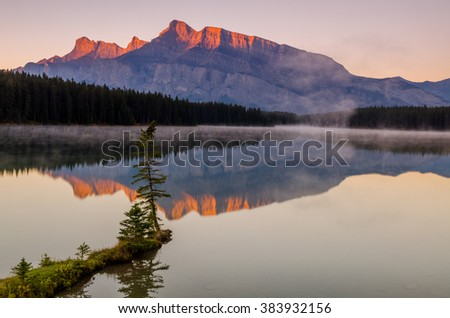First rays of light hitting Mount Rundle at Two Jack Lake