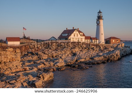 First Rays of Sunlight strike the rocks making them glow orange-red at the Portland Head Lighthouse on Cape Elizabeth - stock photo
