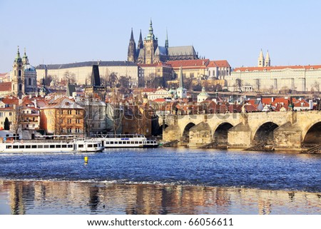 First Snow in Prague, gothic Castle and St. Nicholas' Cathedral with the Charles Bridge in the sunny Day