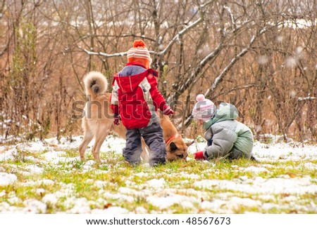 First snow. Little boy and girl playing with dog. - stock photo