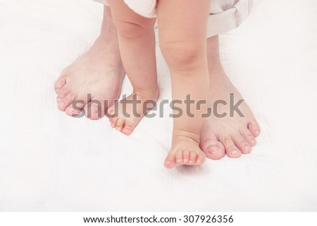 First steps. Baby learning to walk, with help of mothers and fathers. (Soft focus and blurry) - stock photo