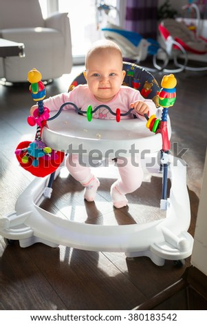 First steps in the baby walker by little baby girl - stock photo