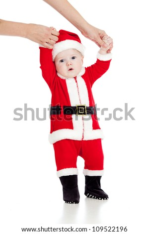 first steps of child dressed as Christmas Santa claus - stock photo