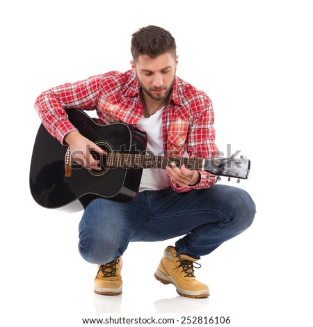 First steps on guitar. Guitarist in red lumberjack shirt crouching and play the black acoustic guitar. Full length studio shot isolated on white.