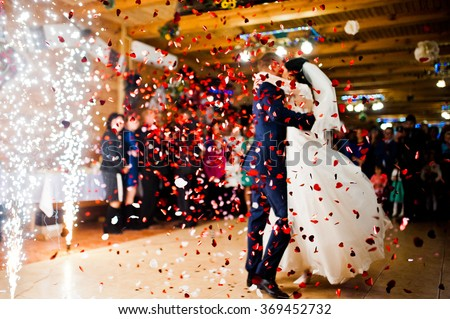 First wedding dance with fireworks and confetti, blured focus - stock photo