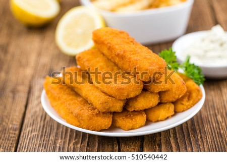 Fisch Sticks (close-up shot) on an old wooden table (selective focus)