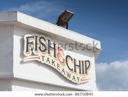 Fish and chip takeaway shop sign, on a white building, against a blue sky. Copyspace in sky.