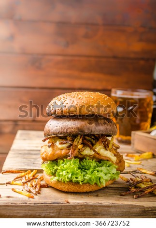 Fish and Chips Burger with fried potato straw and grilled portobello, fresh salad and cold beer