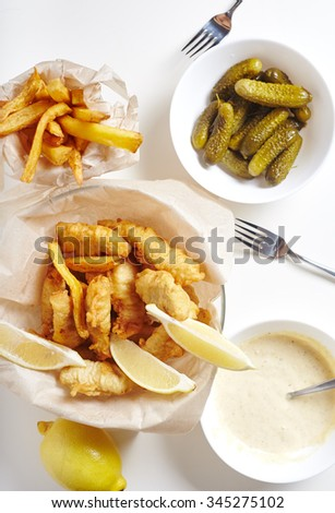 Fish and chips from white fish in paper with mayonaisse sauce, lemon and gherkins - stock photo