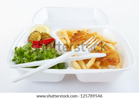 Fish and chips takeout food in plastic box with disposable fork and knife - stock photo