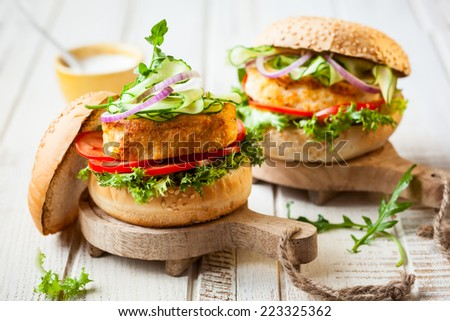 Fish and crab burgers with fresh vegetables on wooden serving boards - stock photo
