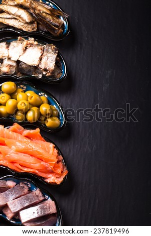 Fish assortment and olives on a plate on a dark background. With space for text - stock photo