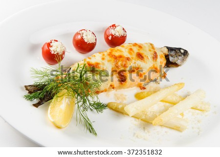 Fish baked under cheese with vegetables - stock photo