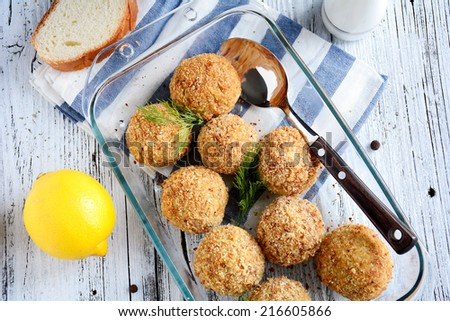 Fish balls baked in glass dish garnished with dill on white and blue napkin served with slice of white bread and lemon - stock photo