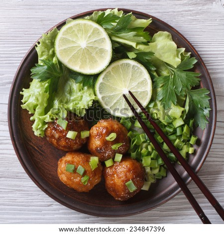 Fish balls in curry sauce on a plate with fresh herbs close up. top view  - stock photo