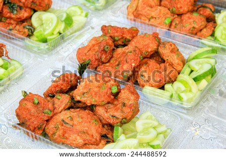 Fish Cake in box, Fried fish cakes with sweet chili sauce and vegetables. Thai Appetizers. Favorite food of Thailand. Local name is Tod-mun. Thai Street Food  - stock photo