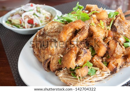 Fish, chopped into pieces and fry with oil.
