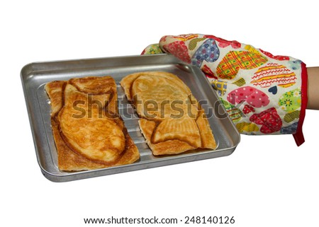 Fish Croissant  in cake tin with oven glove - stock photo