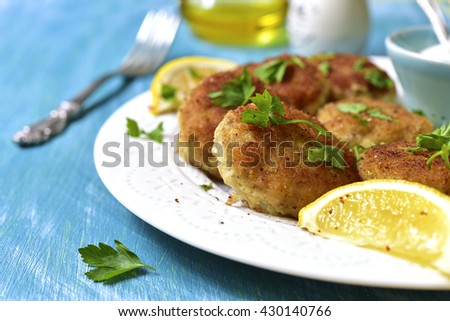 Fish croquettes on a white plate on blue wooden background.