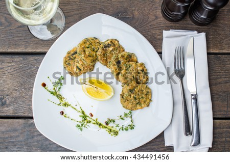 Fish cutlets and wine - tasty and healthy dinner. Plate with fish close-up on a wooden table .