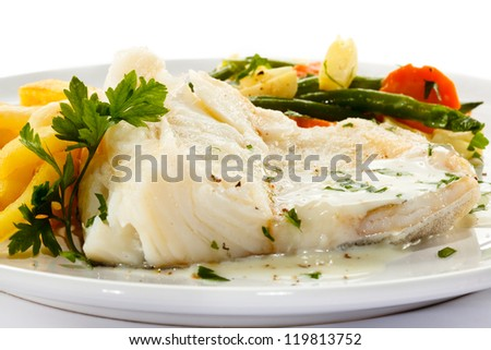 Fish dish - fish fillet in sauce and vegetables - stock photo