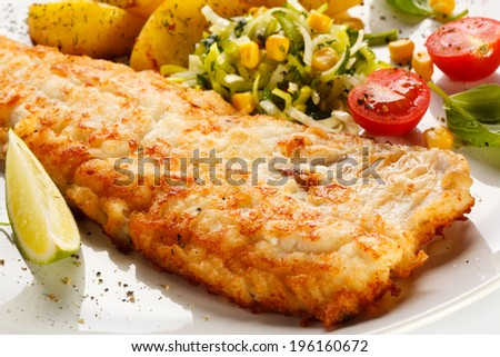 Fish dish - fried fish fillet with baked potatoes and vegetables