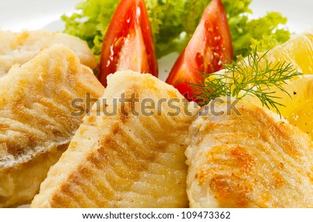 Fish dish - fried fish fillet with vegetables - stock photo