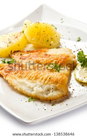 Fish dish - fried fish fillets, boiled potatoes and vegetable salad - stock photo