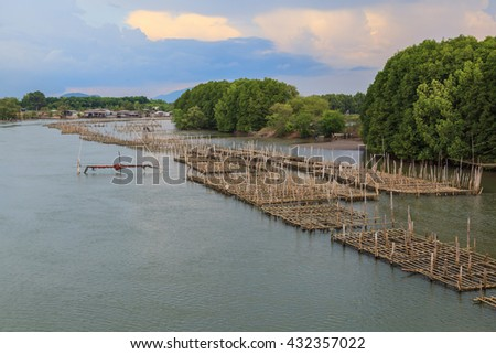 Fish farm with coop in long river, Thailand - stock photo