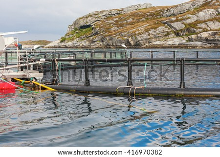 Fish farming in cages at the coast - stock photo
