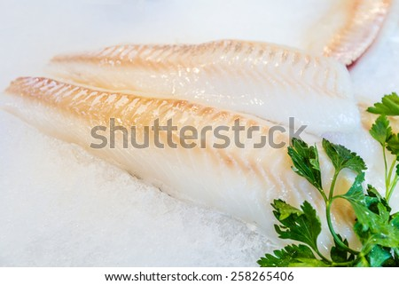 Fish fillet is laid out on ice - stock photo