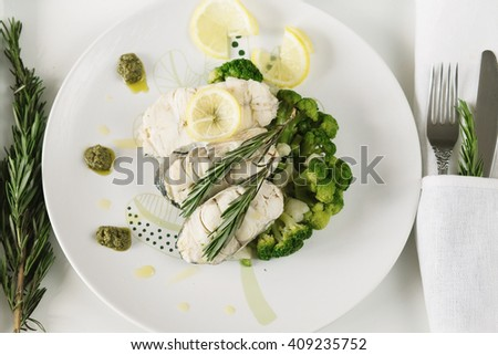 Fish fillet with vegetables and lemon and rosemary on white plate - stock photo