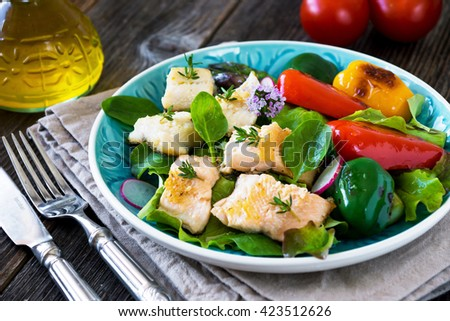 Fish fillets with vegetables on wooden background - stock photo