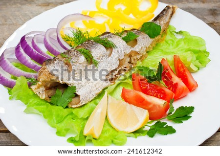 fish hake baked with vegetables on a plate - stock photo